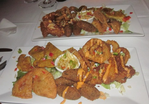 Two platters of fried appetizers with Haitian cole slaw.